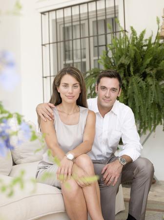 Smiling couple sitting on sofa
