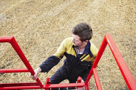 scaling ladder: Farmer climbing machinery ladder