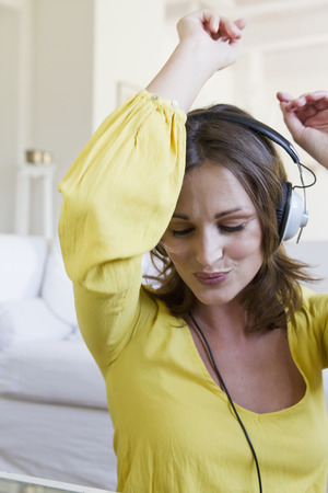 Smiling woman dancing to headphones