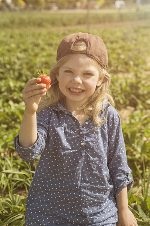 Girl holding fresh picked strawberry