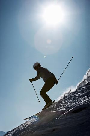 sun energy: Skier coasting on snowy slope