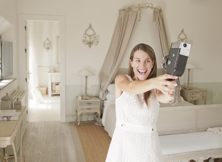 antiquity: Woman using video camera in bedroom LANG_EVOIMAGES