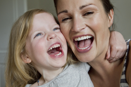 enthusiastically: Close up of mother and daughter laughing