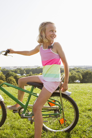 Girl sitting on bicycle in grass
