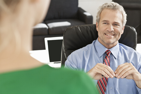 Businessman talking to colleague at desk