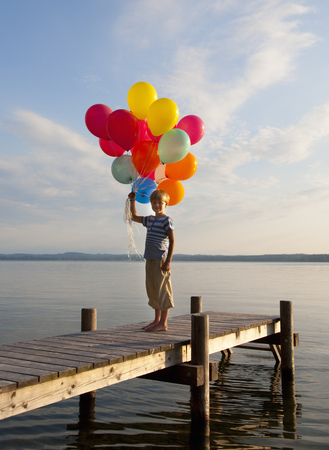 Boy holding balloons on wooden pier