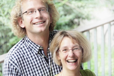 equivalents: Smiling couple standing outdoors