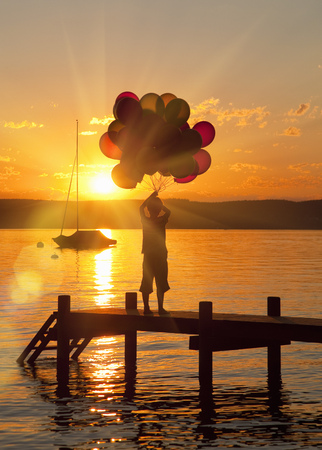 Boy holding balloons on wooden dock LANG_EVOIMAGES