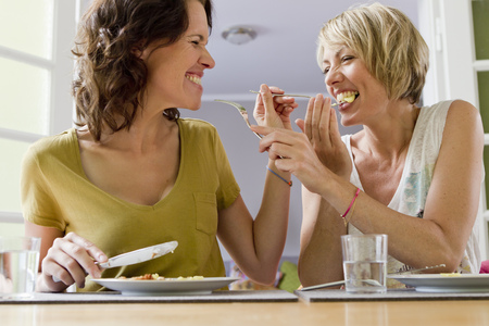 mischievious: Smiling women having lunch together