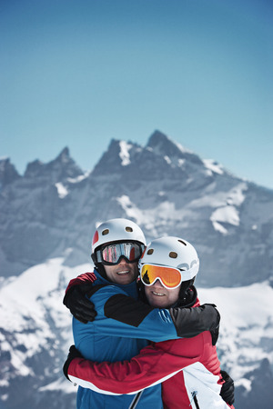 Skiers hugging on snowy mountain LANG_EVOIMAGES
