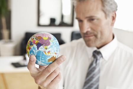 Businessman holding miniature globe