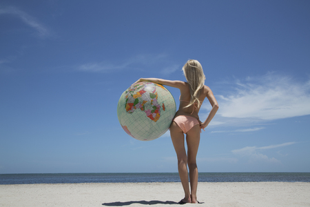 Woman holding globe on beach