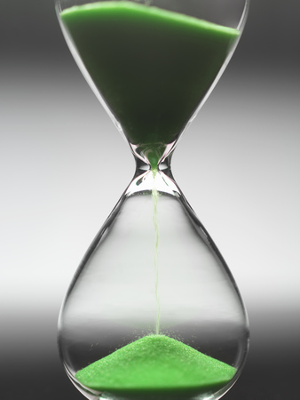 Green sand pouring through hourglass