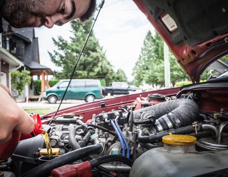 adds: Man working on car engine
