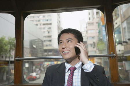 communicated: Businessman on cell phone on bus LANG_EVOIMAGES