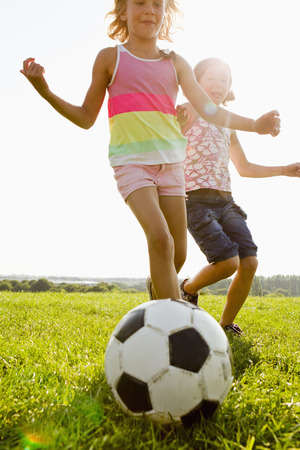 Girls playing soccer in field LANG_EVOIMAGES
