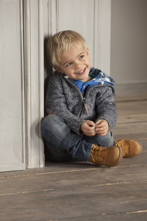 bashfulness: Boy sitting on wooden floor