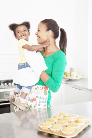 enthusiastically: Mother and daughter laughing in kitchen
