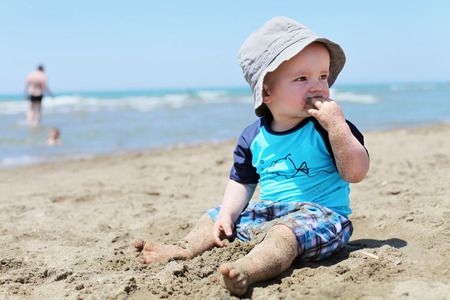 enclose: Toddler eating sand on beach LANG_EVOIMAGES