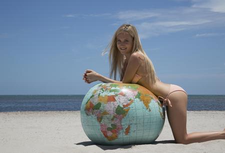 Woman in bikini leaning on globe
