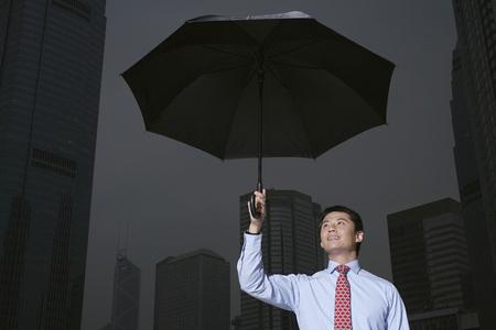drizzling rain: Businessman with umbrella on city street