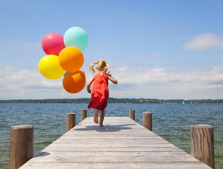 Girl holding balloons on wooden pier