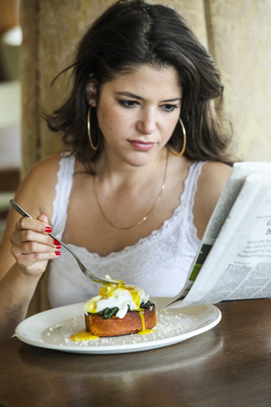 somber: Woman reading newspaper at breakfast LANG_EVOIMAGES