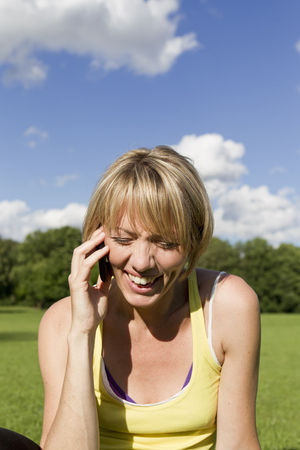Woman laughing on cell phone outdoors LANG_EVOIMAGES