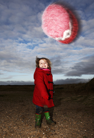 tosses: Girl playing with fuzzy hat outdoors