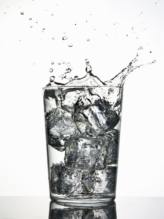 refreshed: Ice cubes splashing into fizzy drink LANG_EVOIMAGES