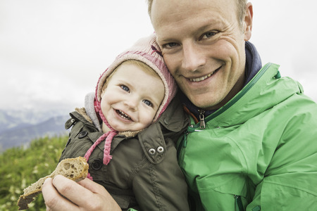 close up food: Father holding daughter outdoors