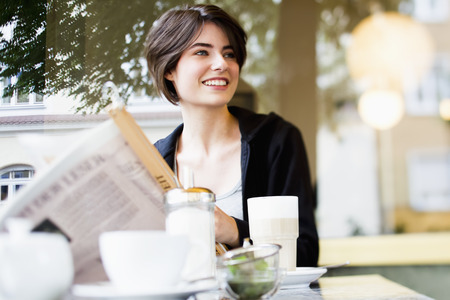 Woman reading newspaper in cafe LANG_EVOIMAGES