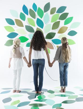 Girls writing on tree on wall
