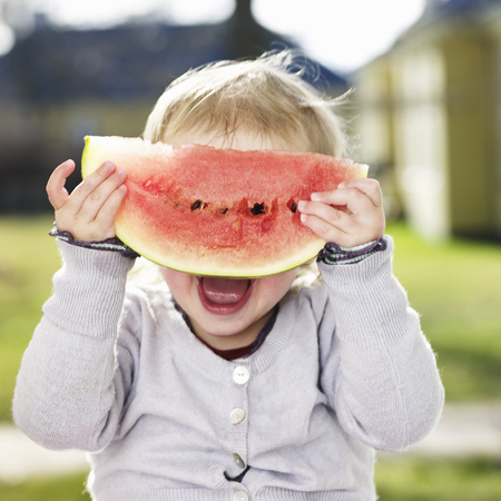 Toddler girl playing with watermelon LANG_EVOIMAGES