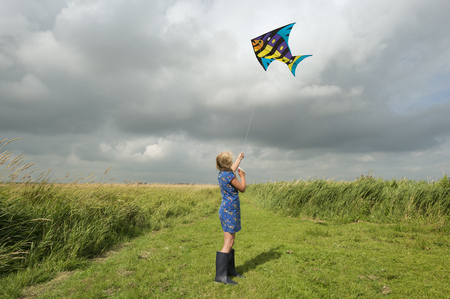 gratify: Girl flying kite in rural field