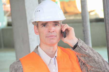responded: Businessman in hard hat on cell phone LANG_EVOIMAGES