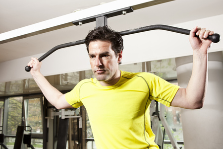 somber: Man using exercise equipment at gym