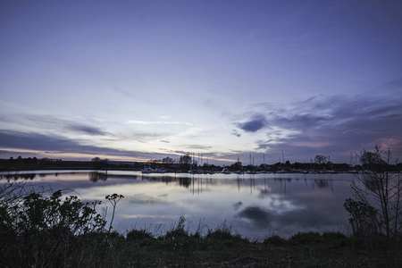 Blue sky reflected in still rural river