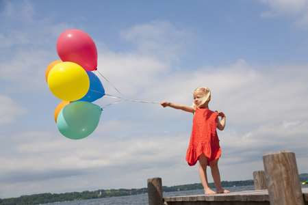 gratify: Girl holding balloons on wooden pier