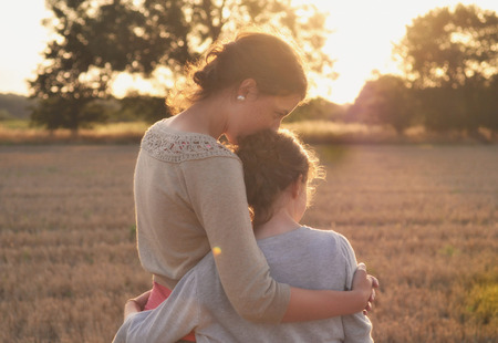Mother and daughter hugging in field