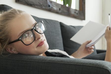 posed: Teenage girl reading on sofa LANG_EVOIMAGES