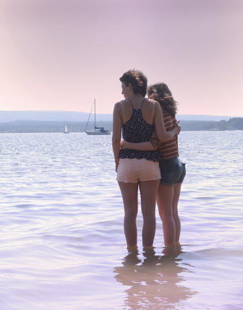 Mother and daughter standing in ocean LANG_EVOIMAGES