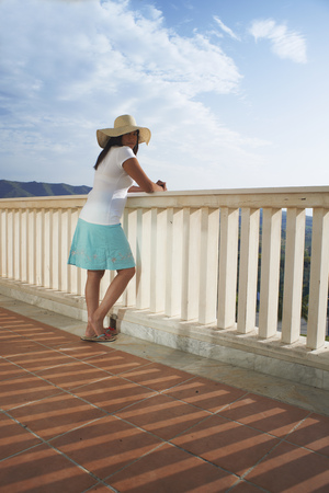 Woman admiring view from balcony LANG_EVOIMAGES