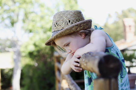 Girl leaning on wooden fence