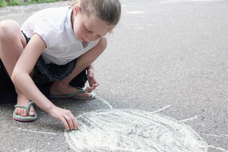 pleasing: Girl drawing sun on sidewalk in chalk LANG_EVOIMAGES