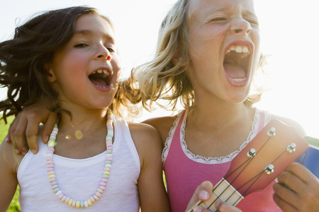 musically: Girls singing together outdoors LANG_EVOIMAGES