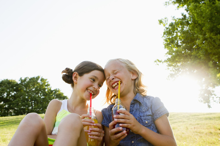 low spirited: Laughing girls drinking juice outdoors LANG_EVOIMAGES