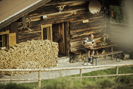leaning by barrier: Man reading in porch of log cabin LANG_EVOIMAGES