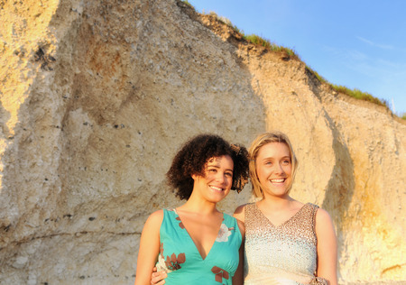 gratify: Smiling women standing by cliff