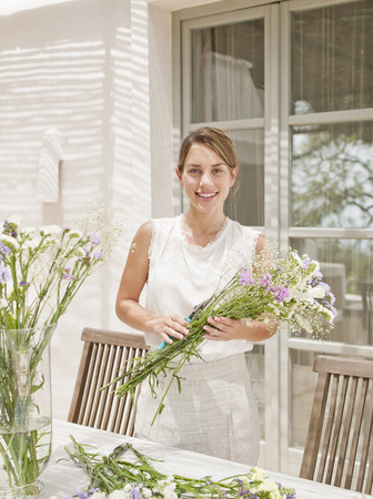 proudly: Woman arranging flowers in kitchen